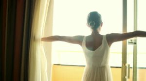 stock-footage-woman-stands-near-window-and-opens-curtains-in-the-morning